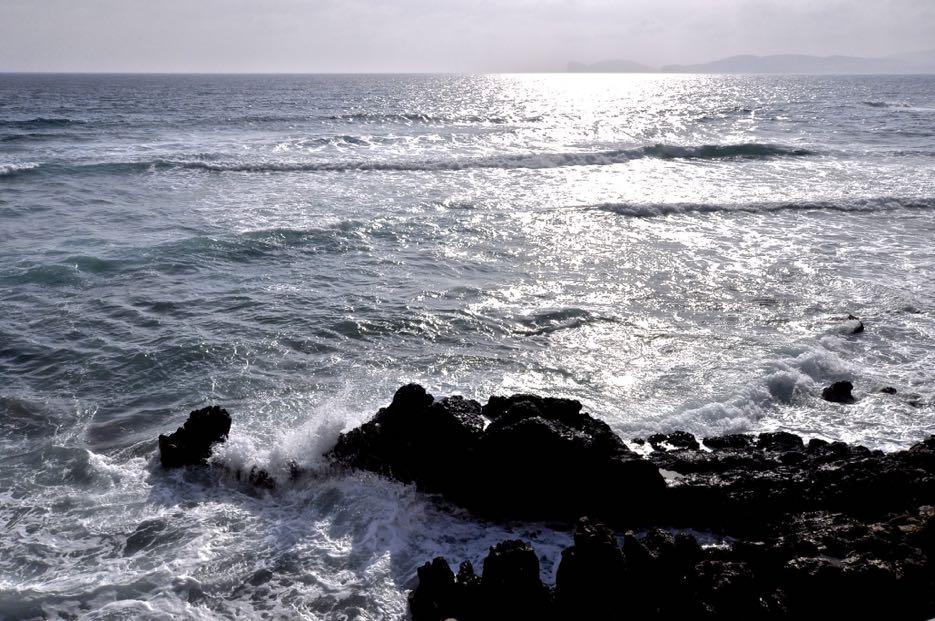 Die Wellen schlagen kraftvoll gegen die Felsen vor der Küste. Dazu weht ein kräftiger Wind.